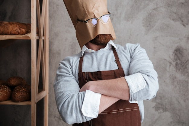 Man baker standing with paper bag on head