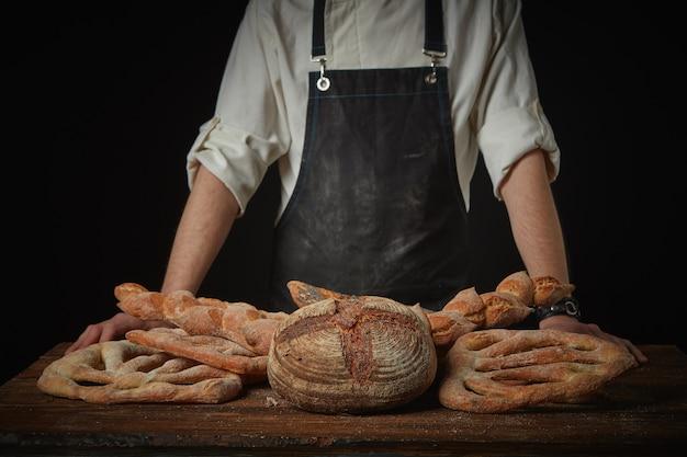 木製の茶色のテーブルにさまざまなパンを持つ男のパン屋