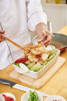 Man baking chicken with vegetables