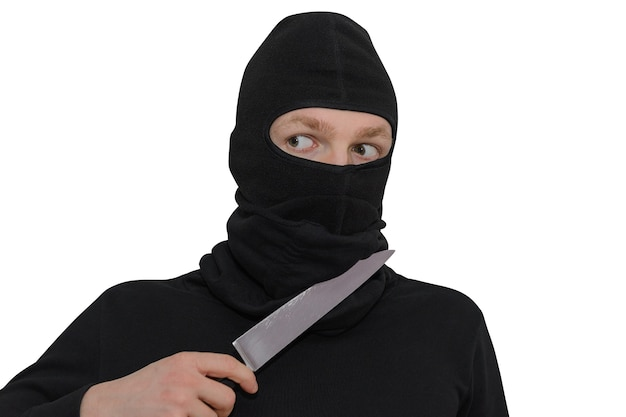 Man in a balaclava with a knife portrait isolated on a white wall