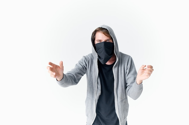A man in balaklava with a hood anonymity crime light background
