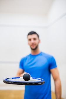 Man balancing a ball on his racket