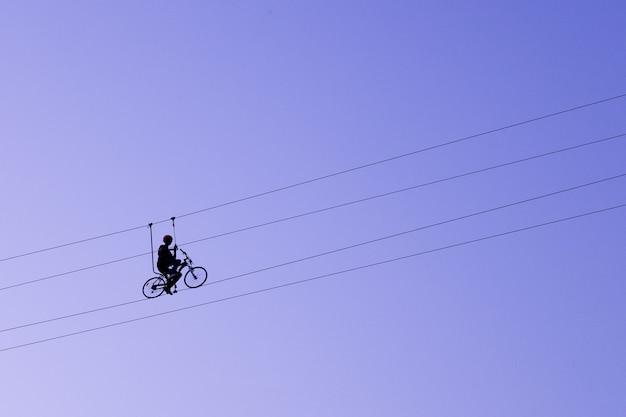 ロープで自転車でバランスをとる男