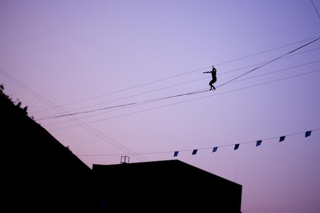 Человек балансирует на веревке против неба