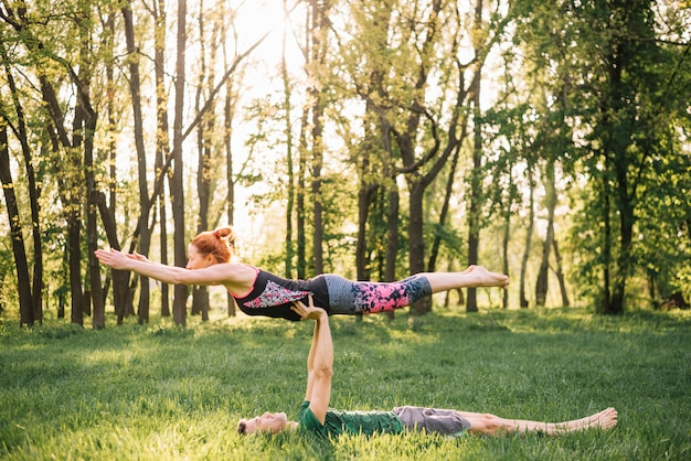 Man balancing woman on his hand while doing yoga in grassy field