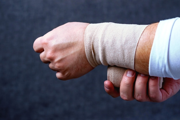 A man bandages his hand with a sports bandage