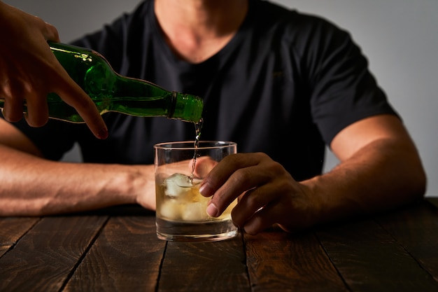 Man at a bar drinking alcohol. concept of alcoholism and drinking addiction.