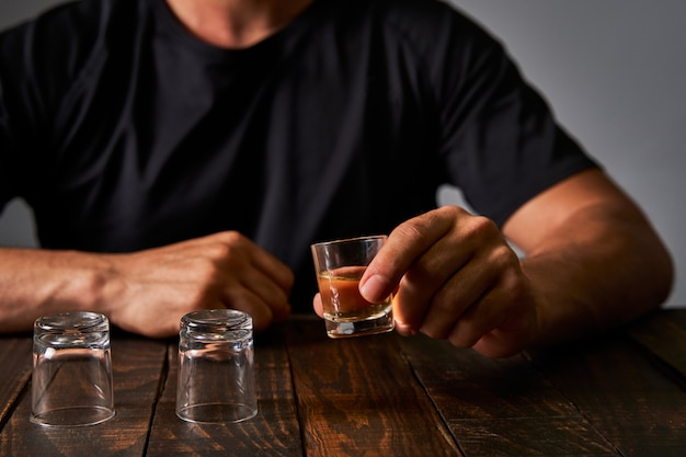 Man at a bar drinking alcohol in shot glasses. concept of alcoholism and drinking addiction.