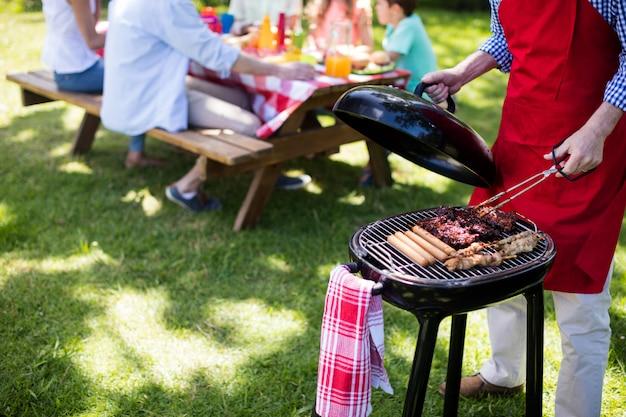 Мужчина готовит барбекю в парке