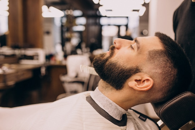 Man at a barbershop salon doing haircut and beard trim