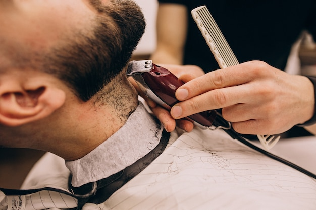 Man at a barbershop salon doing haircut and beard trim