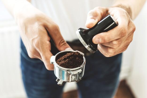 コーヒーを調理する準備ができている挽いたコーヒーでコーヒータンパーを保持している男のバリスタ。閉じる