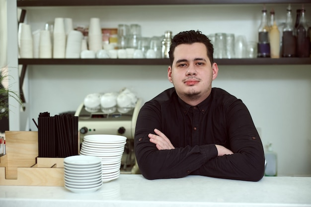 The man barista posing with his arms folded on the bar