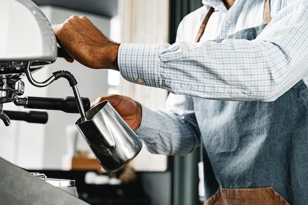 Мужчина бариста готовит кофе на профессиональной кофемашине