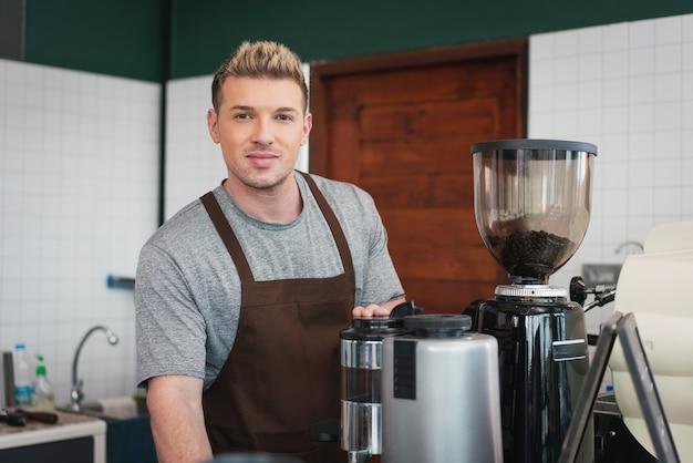 コーヒー ショップのコーヒー マシンの後ろに立っている男性バリスタ