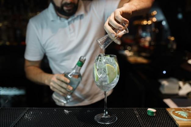 Мужчина-бармен готовит восхитительный коктейль с добавлением белого вина, кубиков льда и ломтиков яблока.