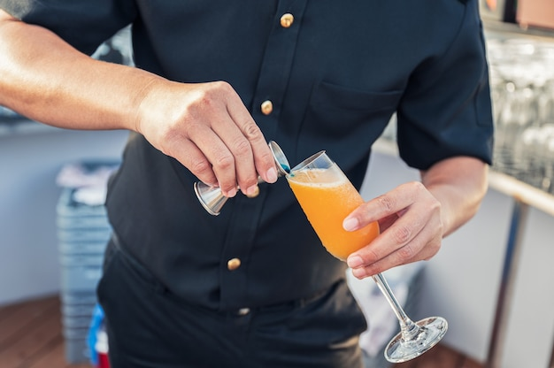 Man bartender mixing cocktail with jugger pouring on wine glass at rooftop bar