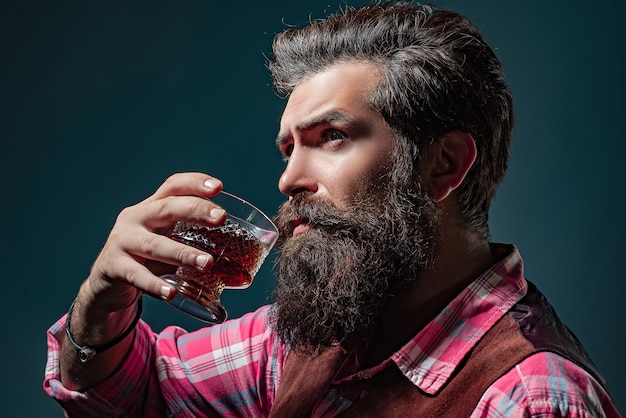 Man bartender with beard holds glass brandy. sommelier tastes expensive alcohol drink