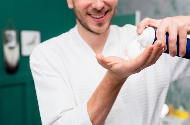 Man in bathrobe spraying shaving foam in hand