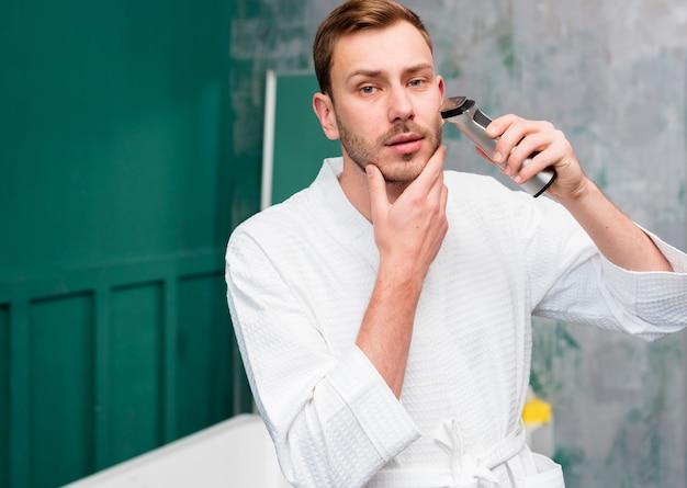 Man in bathrobe using trimmer