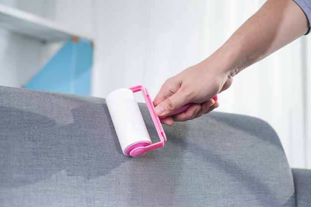 Man to be cleaned with an adhesive roller