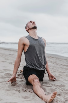 Uomo sulla spiaggia che fa la divisione nella routine di yoga