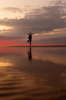 Man on the beach doing yoga or training physical and breathing practices in nature skein beach at