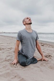 Man on the beach exercising yoga positions