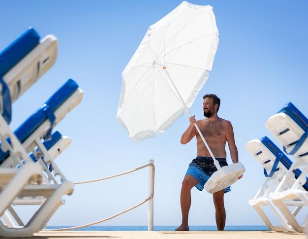 Man on beach jetty moving parasol