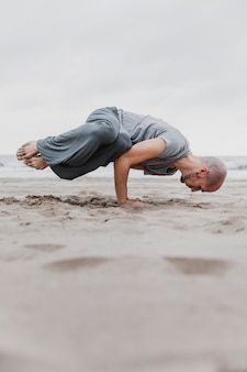 Man on the beach practicing yoga positions