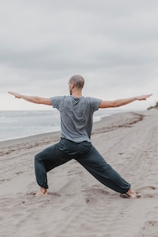 Man on the beach practicing yoga stretching