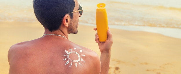 A man on the beach with sunscreen on his back