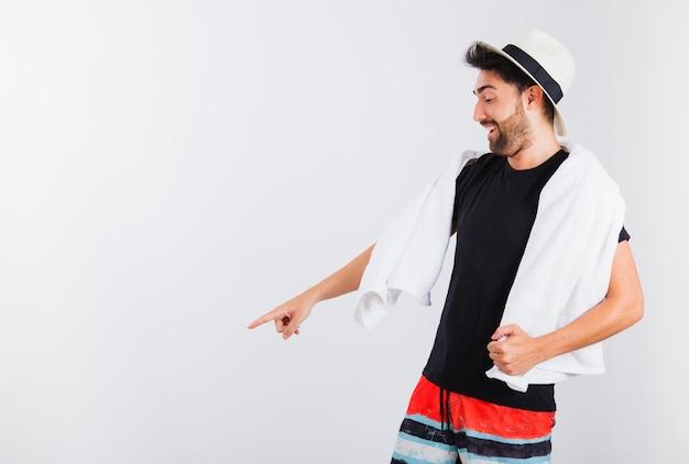 Man in beachwear pointing down