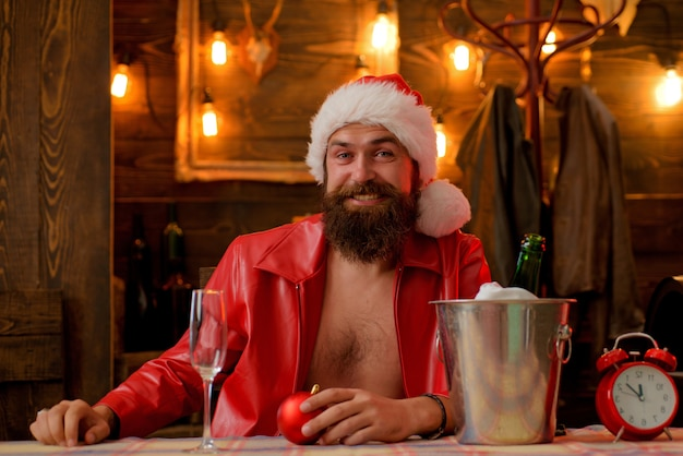 赤い帽子をかぶった男のひげを生やしたヒップスターサンタは、シャンパンドリンクで祝います。クリスマス休日。クリスマスイブに孤独。明けましておめでとうございます。飲む時間。男らしい残忍なサンタレザージャケット。残忍なサンタクロース。
