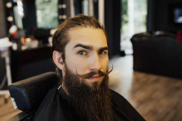 Man bearded hipster in stylish trendy barber shop.