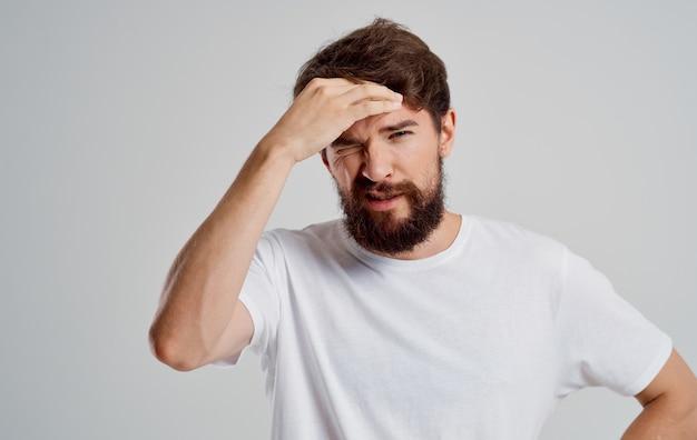 Бородатый мужчина в белой футболке держит голову недовольство эмоциями депрессии.