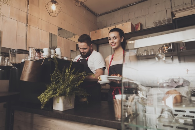 Man and beautiful girl barista behind the counter