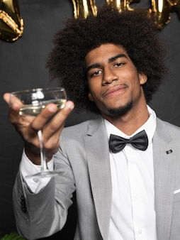 Man in a beautiful party suit holding a glass of champagne
