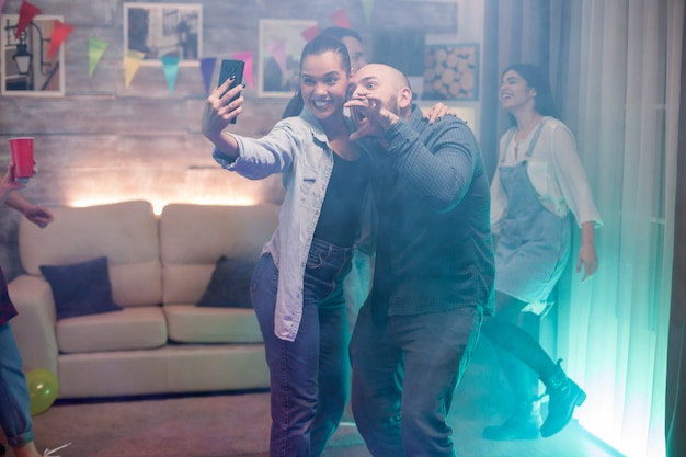 Man and beautiful woman using smartphone taking a selfie while partying with their friends.