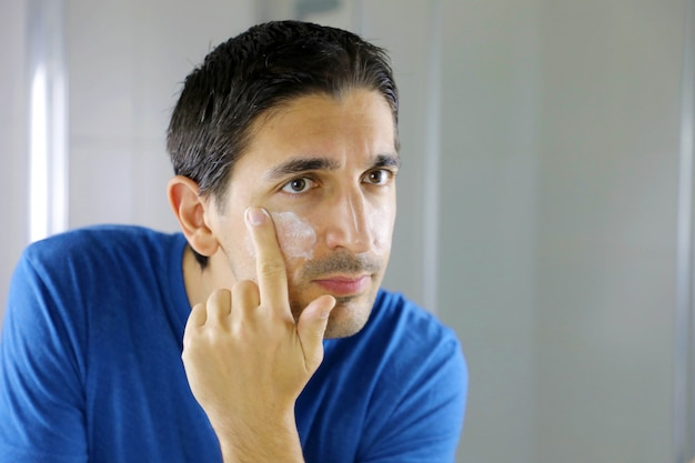 Man beauty applying face cream in home bathroom looking in the mirror