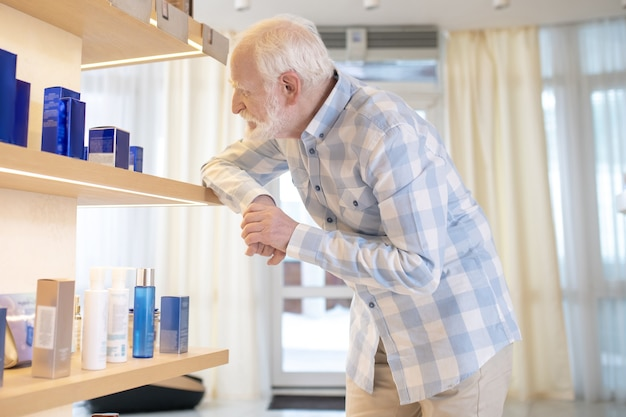 Man in beauty shop. gray-haired man in a plaid shirt in choosing beauty products in a beauty salon