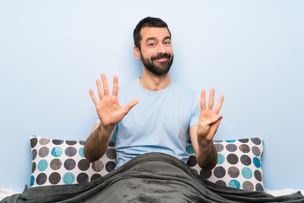 Man in bed counting eight with fingers