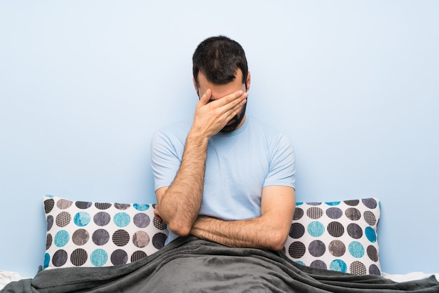 Man in bed covering eyes by hands. do not want to see something