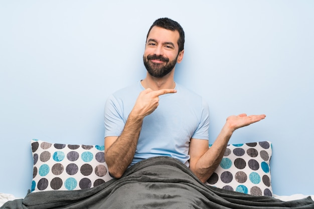 Man in bed holding copyspace imaginary on the palm to insert an ad