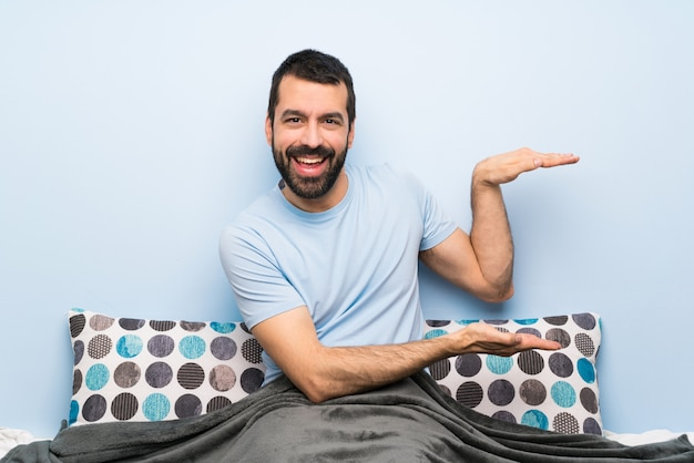 Man in bed holding copyspace to insert an ad