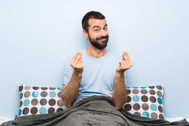 Man in bed making money gesture
