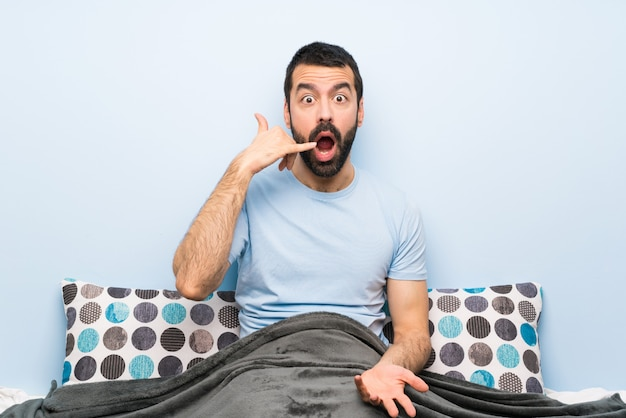Man in bed making phone gesture and doubting