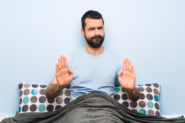 Man in bed making stop gesture and disappointed