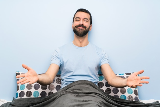 Man in bed presenting and inviting to come with hand