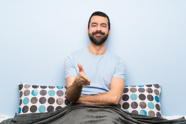 Man in bed shaking hands for closing a good deal